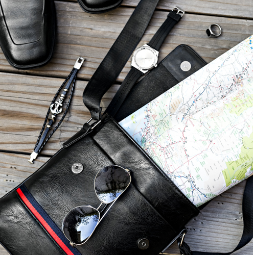men's cross body bag with shoes, watch, sunglasses, ring and map on wood table.